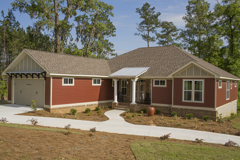 Colors are critical when creating a sense of coziness, and warm hues are the way to go. This home is clad in HardiePlank lap siding in Countrylane Red with the HardiePanel vertical siding in Monterey Taupe and HardieTrim® boards in Sandstone Beige. The warm red paired with the soft neutrals provides an inviting farmhouse feel.